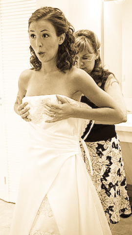 Beth holds everything in place while her mom ties her wedding dress